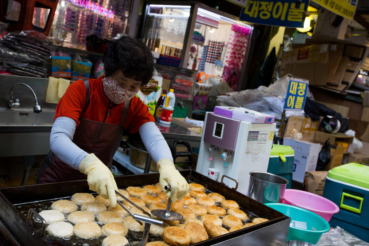 A vendor cooks hotteok, a Korean sweet pancake, at a stall at the Seomun Market in Daegu, South Korea, on Saturday, Nov. 12, 2016. The disenchantment with President Park Geun-hye in her hometown of Daegu signals a wider shift in the nation's political landscape, where regional loyalties often hold greater sway among the electorate than policy platforms. Photographer: SeongJoon Cho/Bloomberg